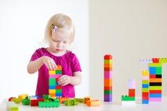 Het leuke peutermeisje plaing met kleurrijke blokken Stock Afbeelding