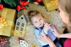 Het leuke portret van weinig baby viert Kerstmis Nieuwjaar` s vakantie De jongen in boytie ligt onder de boom en het spelen met m Royalty-vrije Stock Foto's