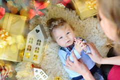 Het leuke portret van weinig baby viert Kerstmis Nieuwjaar` s vakantie De jongen in boytie ligt onder de boom en het spelen met m Stock Foto