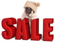Het leuke pug puppyhond hangen met poten op groot rood die verkoopteken, op witte achtergrond wordt geïsoleerd Royalty-vrije Stock Afbeeldingen