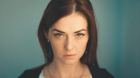 Het leuke roodharigemeisje onderzoekt de camera Modern meisje in een stedelijk milieu Sproetengezicht royalty-vrije stock fotografie