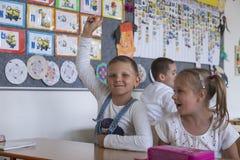 Het leuke schoolmeisje heft op haar hand op Stock Foto