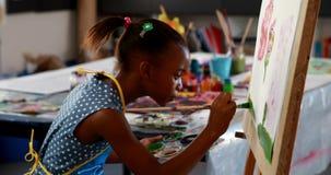 Het leuke schoolmeisje schilderen op canvas 4k stock video