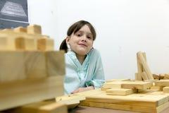 Het leuke schoolmeisje spelen met houten raadsels Stock Foto