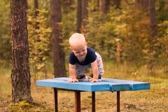 Het leuke smirking peuter spelen op de bank in het de herfst of de zomerpark royalty-vrije stock fotografie