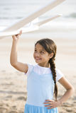 Het leuke Spaanse meisje spelen met stuk speelgoed vliegtuig op strand stock afbeelding