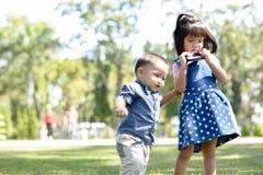 Het leuke spel van jonge geitjesbroers samen De jongen beweegt zich rond haar zuster Royalty-vrije Stock Fotografie