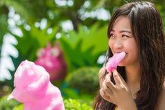 Het leuke Thaise meisje eet roze candyfloss stock fotografie
