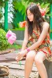 Het leuke Thaise meisje zit terwijl het houden van roze candyfloss royalty-vrije stock fotografie