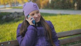 Het leuke tienermeisje glimlachen die op de telefoon spreken Tand steunen Slow-motion stock footage