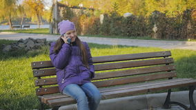 Het leuke tienermeisje glimlachen die op de telefoon spreken Tand steunen Slow-motion stock videobeelden