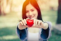 Het leuke tienermeisje het glimlachen tonen gevend het concept van de hartliefde stock foto