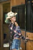 Het leuke tienermeisje in paardrijdenkledij stelt in schuur stock foto