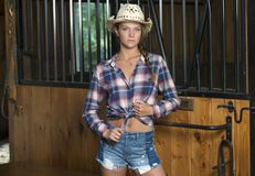 Het leuke tienermeisje in paardrijdenkledij stelt in schuur royalty-vrije stock foto