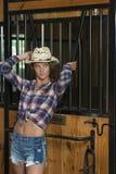 Het leuke tienermeisje in paardrijdenkledij stelt in schuur royalty-vrije stock foto's