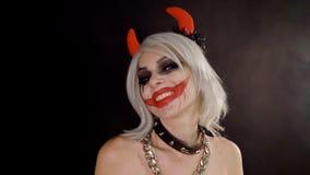 Het leuke vriendelijke seksuele duivelsmeisje verleidt, flirt, gooi, kus, zit op donkere zwarte achtergrond in rook De vrouw van  stock footage