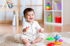 Het leuke vrolijke baby spelen met kleurrijk stuk speelgoed thuis stock afbeelding