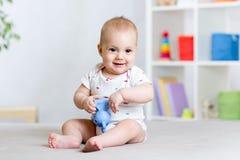 Het leuke vrolijke baby spelen met stuk speelgoed thuis royalty-vrije stock foto's
