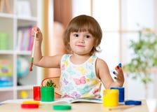 Het leuke vrolijke kindmeisje met vingers schilderde in heldere kleuren stock foto