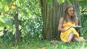 Het leuke vrouwenmeisje in gele kleding zit onder oude boom geniet van gelezen nieuw boek in de zomerpark 4K stock footage