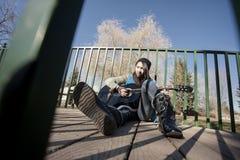 Het leunen tegen traliewerk met gitaar Stock Fotografie