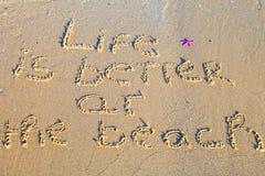 Het leven is beter op het strand in het zand wordt geschreven dat Royalty-vrije Stock Foto