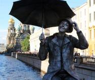 Het leven standbeeld van een jongen met paraplu op een brug over Griboyedov-Kanaal stock foto