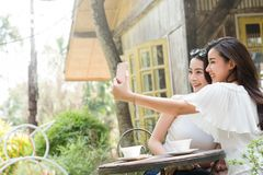 Het leven van generatiey tieners hangt uit in slimme het gebruik van de koffiewinkel stock afbeelding