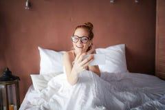 Het levendige vrouw ontspannen in bed die aangezien zij aan een vraag op haar mobiele telefoon met haar rood haar lachen luistert stock foto's