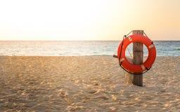 Het levenspreserver op zandig strand stock afbeelding