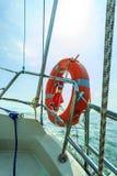 Het levenspreserver van de reddings rode reddingsboei spaardersring op zeilboot Stock Afbeelding