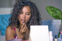 Het levensstijlportret van jonge gelukkige en mooie Latijns-Amerikaanse vrouw die zorgvuldig lipgloss schetst op haar lippen toep royalty-vrije stock foto's