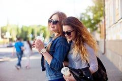 Het levensstijlportret van twee gelukkige vriendenmeisjes loopt lachbespreking en drinkt limonade die in heldere kleren en zonneb stock foto