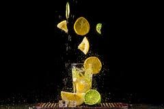 Het levitatie ondergaan van plakken van citroen en kalk, een plons van water Stock Foto