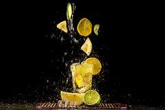 Het levitatie ondergaan van plakken van citroen en kalk, een plons van water Royalty-vrije Stock Afbeeldingen