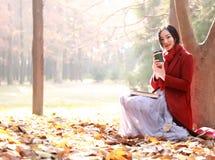 Het lezen in aard is mijn hobby, Meisje met boek en thee in het de herfstpark Stock Foto's
