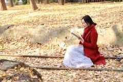 Het lezen in aard is mijn hobby, zit het meisje Gelezen boek op het sporenhoogtepunt van Ginkgo-bilobabladeren royalty-vrije stock foto
