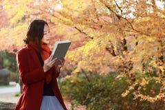 Het lezen in aard is mijn hobby, zit het mooie meisje Gelezen boek op steen in park stock afbeelding