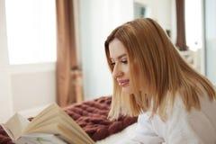 Het lezen in Bed Jong mooi blondemeisje die op het bed liggen en een boek lezen De hobby en ontspant royalty-vrije stock afbeeldingen