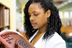 Het lezen in bibliotheek Stock Foto's
