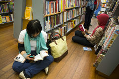 Het lezen bij Boekhandel Stock Afbeeldingen