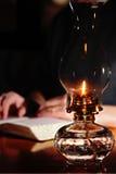 Het lezen door Uitstekende Lamplicht Stock Foto's