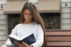 Het lezen in een Bank Stock Foto