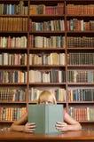 Het lezen en het verbergen achter een boek Stock Fotografie