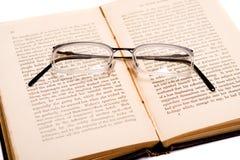 Het lezen - glazen op een open boek Stock Foto's