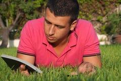 Het lezen in het gras Stock Foto