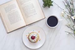 Het lezen met een te ontspannen cupcake royalty-vrije stock afbeeldingen