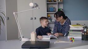 Het lezen met leraar - een basisschooljongen leest hardop aan haar leraar Leraarszitting bij bureau naast mannelijke student stock footage