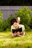 Het lezen van e-boek in het park Stock Afbeelding