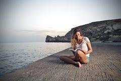 Het lezen van een boek bij het strand Stock Afbeeldingen